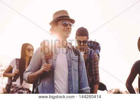 Friends hiking. Group of young people with backpacks walking together and looking happy