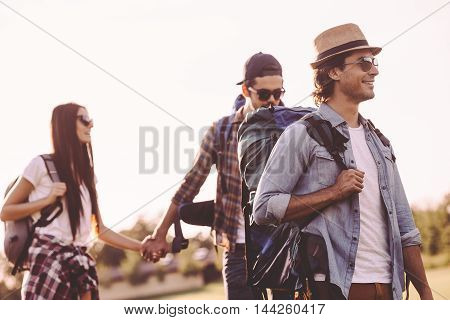 Summer hike with friends. Young people with backpacks walking together and looking happy