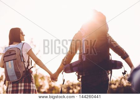 Discovering new places together. Rear view of young couple with backpacks walking together and holding hands