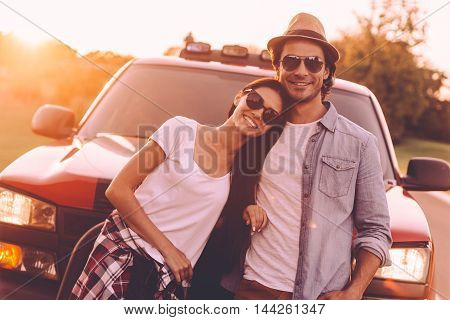Ready to road trip. Beautiful young smiling couple bonding to each other and leaning at their pick-up truck