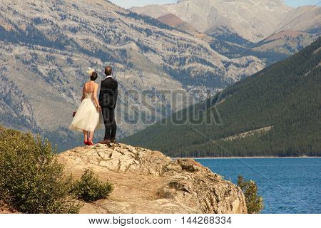 Married couple looking up at the Rocky mountains on a turquoise lake. Room for copy.