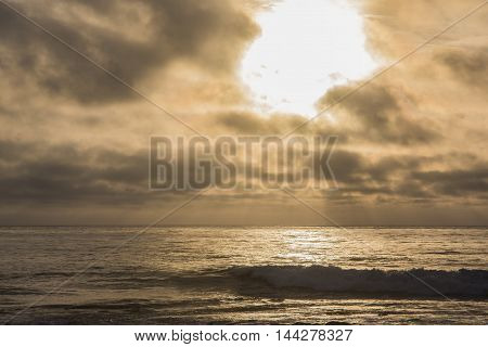 Dramatic pink yellow moody sunset with god rays on pacific ocean beach