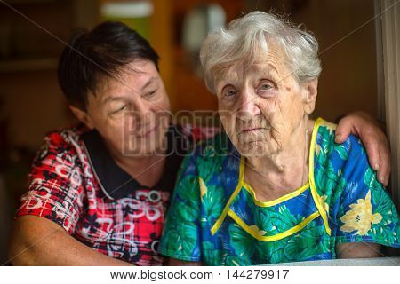 Sad elderly woman, in background hugging adult daughter.
