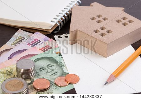 Toy House For Thai Banknotes As Background. Wood House With Thai Coins And Banknote.