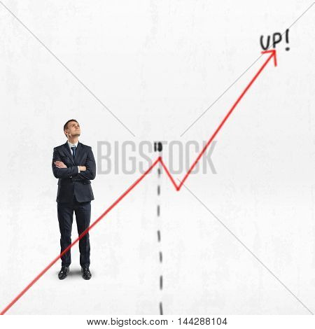 Businessman stands with folded arms looking upwards behind big rising diagram isolated on white background. Succesful management. Supervision and control. Investment and finance.