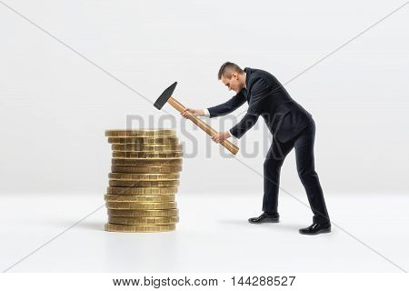 Side view of a businessman crashing big stack of golden coins with hammer, isolated on white background. Making money. Business staff.
