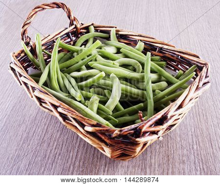 Green beans in basket over wooden table horizontal image