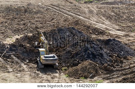 Excavator carries earth works. Construction of road in mountainous terrain.