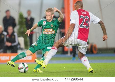 VIENNA, AUSTRIA - JULY 29, 2015: Florian Kainz (SK Rapid) and Kenny Tete (Ajax) fight for the ball in an UEFA Champions League qualification game.