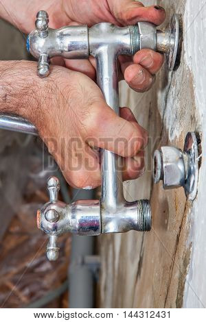 Replace kitchen tap uninstall the old faulty faucet wall mount plumber hands closeup.