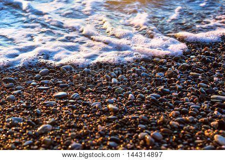 Foam Sea Wave Rushes At Pebble Seashore