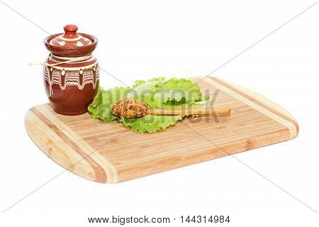 Small pot and spoon with mustard lying on cutting board isolated over white background
