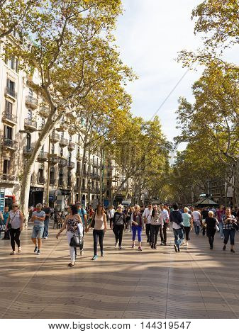 Barcelona - 10 October 2015: A lot of people happy and tourists stroll on the main tourist street of beautiful Barcelona in Catalonia - Rambla October 10 2015 Barcelona Spain