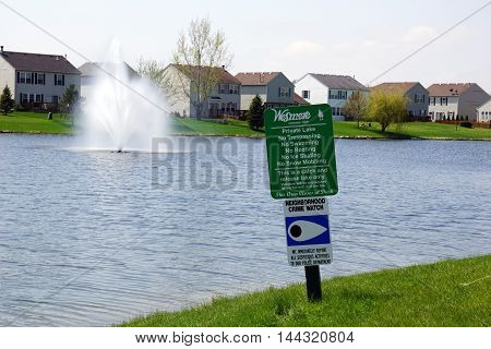 JOLIET, ILLINOIS / UNITED STATES - APRIL 22, 2016: Wesmere Country Club's private lake sign: trespassing, boating, swimming, ice skating, and snow mobiling are all prohibited.