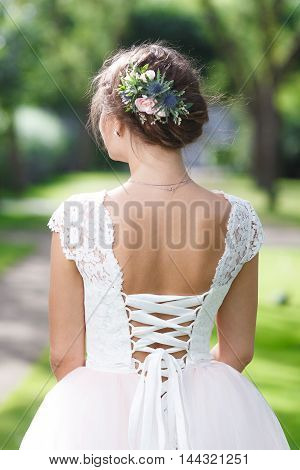 Beautiful bride with fresh flowers in her hair (back view)