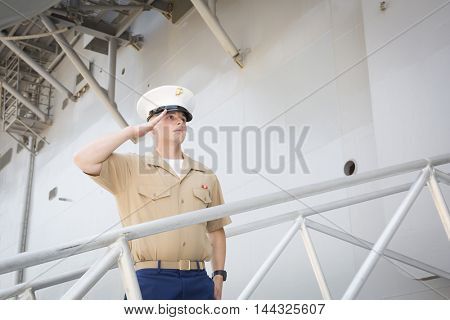 NEW YORK MAY 26 2016: A member of the US Marines salutes as he disembarks the USS Bataan (LDH 5) an amphibious assault ship moored at Pier 88 during Fleet Week NY 2016.