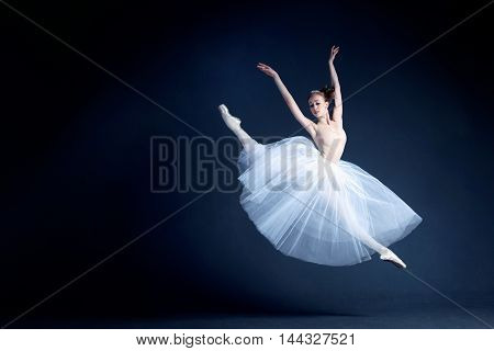 Young ballerina in a beautiful dress is dancing in a dark photostudio