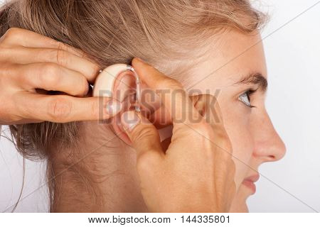 Close up of hands fitting a young woman with hearing aid