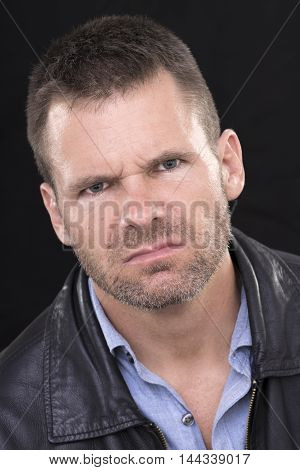 Closeup portrait of angry disgruntled Caucasian man with short hair and stubble with mean expression on black background