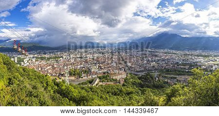 Panorama of Grenoble city and French Alps on the background Rhone-Alpes region France. Picturesque aerial view from Bastille in summer cloudy day