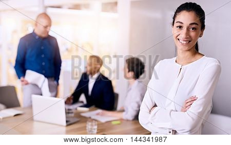 Young multiethnic businesswoman smiling while standing arms crossed in front of the rest of her diverse and dynamic team that she believes in with confidence and can firmly rely on.