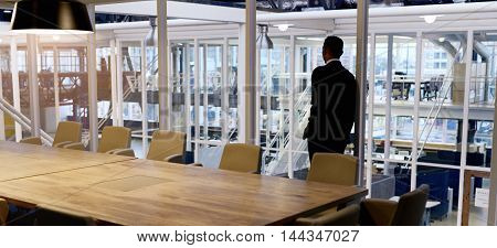 Businessman standing in empty conference room looking out the window, trying to gather his thoughts about possibly having to enter into a merger with his opposition.