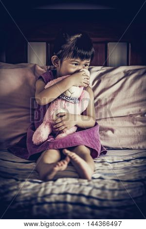 Sad asian child sitting alone on bed with doll in dark bedroom at home. Emotional of depressed girl with a shallow depth of field selective focus. Vignette style. Low key and high contrast effect.