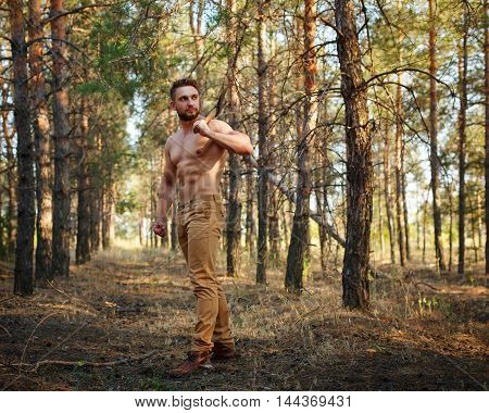 Lumberjack with cleaver walking through forest. Woodcutter with a naked torso. Felling trees. Logging. Manual labor.