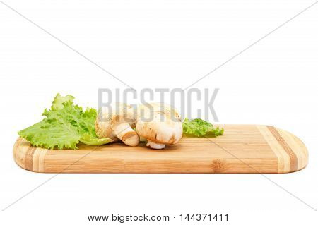 Close view of champignons lying on cutting board isolated over white background