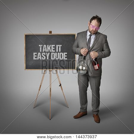 Take it easy dude text on blackboard with businessman and wine bottle