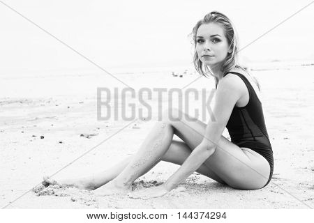 Black and white photo of elegant blonde pretty woman with wet look wearing black swimsuit sitting on the sandy beach near the sea over sky background