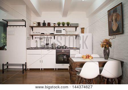 Modern kitchen interior with white brick wall and wooden floor