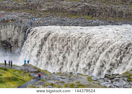 Unidentifiable tourists admire Dettifoss waterfall  in Iceland. Dettifoss is the most powerful waterfall in Europe.