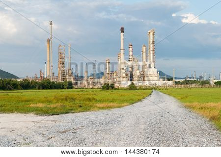 Petrochemical Industry Power With Dirt Road With Green Grass