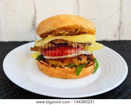 Homemade hamburger with juicy cutlet arugula bacon vegetables and mozzarella.