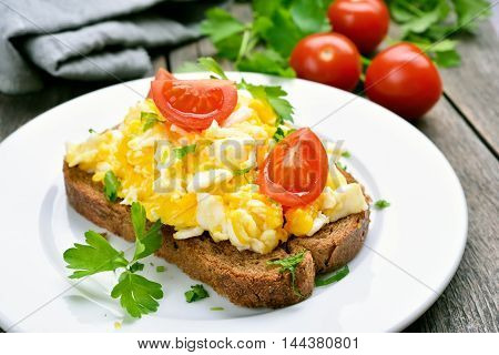 Scrambled eggs and tomato slices on bread close up view