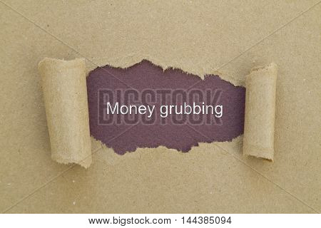 money grubbing word written under torn paper.