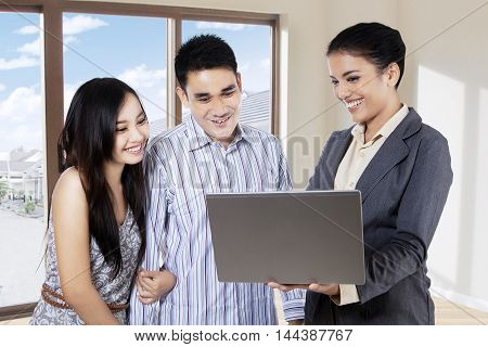 Female realtor showing new house to couple with a laptop computer inside the new house