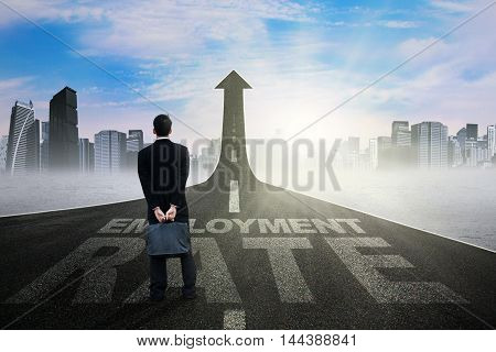 Male job seeker standing on the road with employment rate text and upward arrow