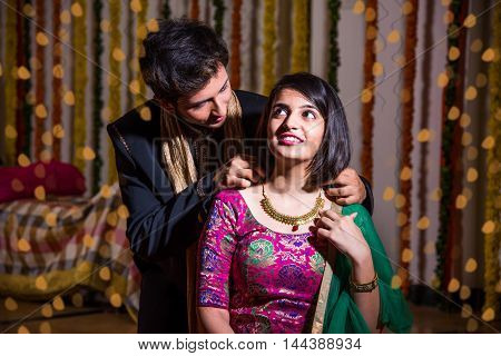 indian husband tying or presenting necklace to his beautiful wife as a diwali gift, indian young couple celebrating diwali festival
