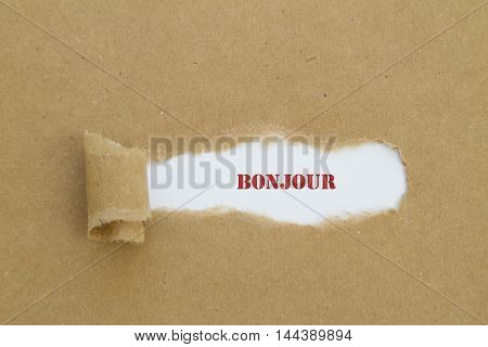 French Bonjour (hello) word written under torn paper.