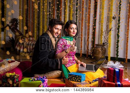 indian young couple and online shopping concept, indian couple shopping online on laptop, e-commerce and diwali festival concept