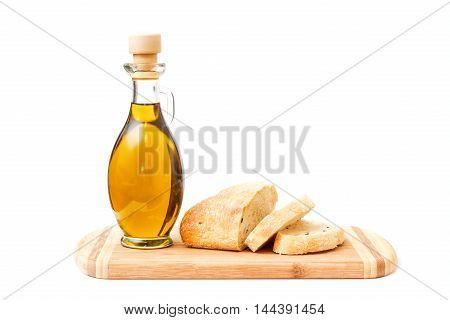 Close view of olive oil and sliced bread standing on cutting board isolated over white background