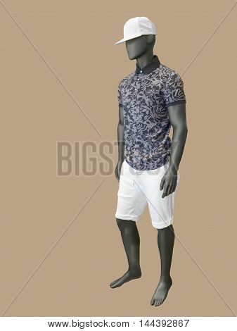 Full length male mannequin dressed in shirt and white shorts isolated on brown background. No brand names or copyright objects.