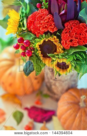 Autumn still life.Autumn bouquet of flowers with pumpkins and leaves .