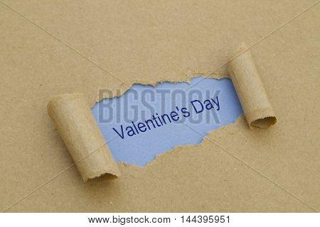 Valentines Day written under torn paper .