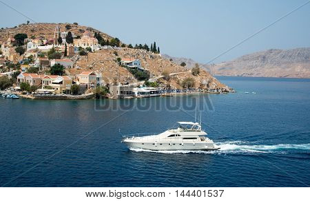 Symi Greece - August 1 2016: Symi town with colorful houses on the hill and luxury yacht entering the marina in the Greek Island of Symi at the Aegean sea.