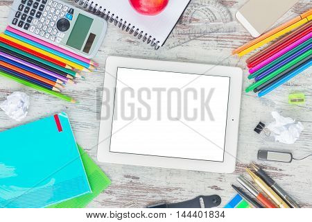 back to school frame with school supplies, copy space on tablet with empty screen on wooden table