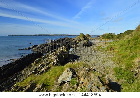A bright and sunny image of the rocky beach of Angle in Pembrokeshire.