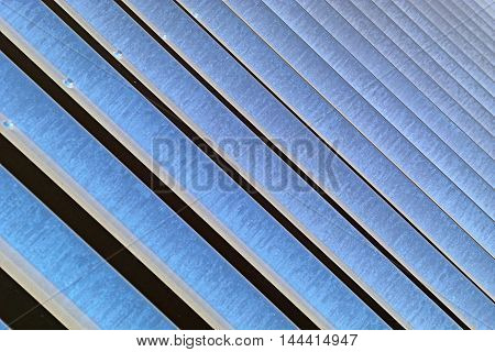 Slanted pale blue metal bars close-up abstract in horizontal 3:2 format.